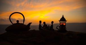 Arabiskt te i traditionell exponeringsglas och kruka på öken på solnedgången Östligt tebegrepp Konstverkgarnering på sand med te arkivfoto