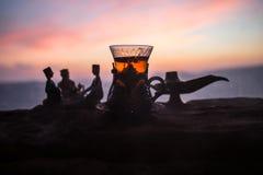 Arabiskt te i traditionell exponeringsglas och kruka på öken på solnedgången Östligt tebegrepp Konstverkgarnering på sand med te royaltyfria bilder