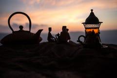 Arabiskt te i traditionell exponeringsglas och kruka på öken på solnedgången Östligt tebegrepp Konstverkgarnering på sand med te arkivbild