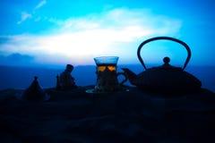 Arabiskt te i traditionell exponeringsglas och kruka på öken på solnedgången Östligt tebegrepp Konstverkgarnering på sand med te royaltyfri bild