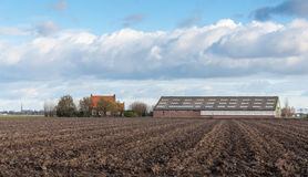 Arable farm in the Netherlands. Cloudy sky above a Dutch farmhouse and barn at a plowed field in autumn Royalty Free Stock Image