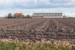Arable farm in the Netherlands. Cloudy sky above a Dutch farmhouse and barn at a plowed field in autumn Royalty Free Stock Photos
