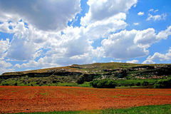 ARABLE FARMLAND FLANKED BY MOUNTAIN. Arable farmland with mountains under sky and cloud Royalty Free Stock Image