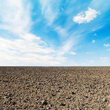 Arable field and clouds in blue sky. Arable field and white clouds in blue sky Stock Photos