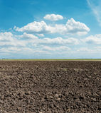 Arable field after harvesting and blue sky. Black arable field after harvesting and blue sky Stock Photography