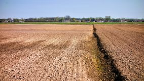 Arable land with village in the background. Arable land from low angle and village in the background Stock Image