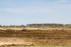 Arable land over blue sky. Tractor preparing land with seedbed cultivator as part of pre seeding activities in early spring season of agricultural works at Royalty Free Stock Image