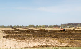 Arable land over blue sky. Tractor preparing land with seedbed cultivator in early spring season of agricultural Stock Image