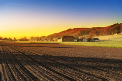 Arable land and pastures in Switzerland. Swiss village surrounded by forests and plowed fields at sunset. Agriculture in Switzerland, arable land and pastures Stock Photos