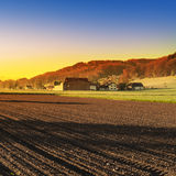 Arable land and pastures in Switzerland. Swiss village surrounded by forests and plowed fields at sunset. Agriculture in Switzerland, arable land and pastures Stock Photo
