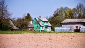 Arable land with a turquoise chalet at the background in Lithuania. Arable land with a cyan lodge at the background and a hothouse in Lithuania Stock Image