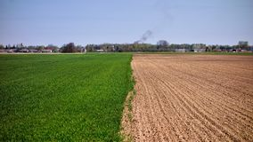 Arable land with village in the background. Arable land from low angle and village in the background Stock Photos