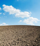 Arable soil and blue sky. With clouds Stock Photos
