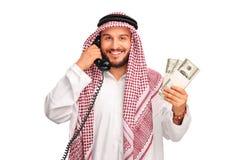 Arabo che parla su un telefono e che tiene soldi Fotografie Stock Libere da Diritti