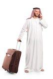 Arabo che trasporta una valigia e che comunica su un telefono Fotografia Stock