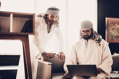 Two Arab businessmen looking on laptop together stock images