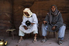 Arabs in Jordan. Two Arabs dressed in traditional Nabatean clothes drink coffee Stock Images