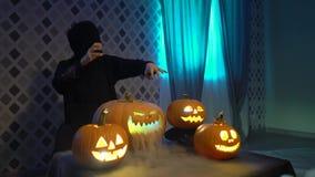 Arabska kobieta w abaya świętuje Halloween z okaleczać śmiesznymi baniami Czarownica czaruje parującej bani, ciska czary zbiory wideo