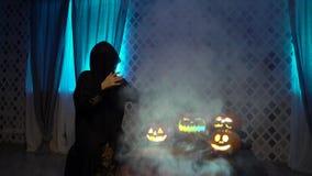 Arabska kobieta w abaya świętuje Halloween z strasznymi śmiesznymi baniami Czarownica czaruje parującej bani, ciska czary zbiory