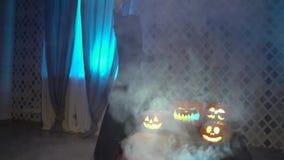 Arabska kobieta w abaya tanach, świętuje Halloween z strasznymi śmiesznymi baniami Czarownica czaruje parującej bani, ciska a zbiory