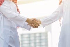 Arabski Biznesowy uścisk dłoni i ludzie biznesu na miasta tle Fotografia Stock