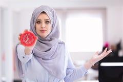 Arabski bizneswoman z zegarem jest opóźniony będący ubranym hijab Obrazy Royalty Free