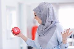 Arabski bizneswoman z zegarem jest opóźniony będący ubranym hijab Zdjęcie Royalty Free