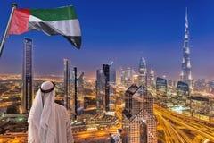 Arabski mężczyzna dopatrywania nocy pejzaż miejski Dubaj z nowożytną futurystyczną architekturą w Zjednoczone Emiraty Arabskie Zdjęcie Stock