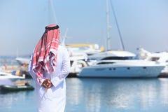 Arabski mężczyzna patrzeje jachtu schronienie obraz stock