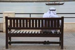 Arabski mężczyzna w dishdasha obsiadaniu na drewnianej ławce przy zatoczką, Dubaj Zdjęcia Stock