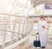 Arabski mężczyzna w podróży pojęciu Młody saudyjski arabski mężczyzna w tradycyjnym odzieżowym odprowadzeniu z walizką na lotnisk Obrazy Stock