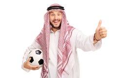 Arabski męski mienie futbol i dawać up kciuk Zdjęcia Stock