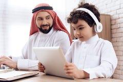 Arabski ojciec pomaga małego syna uczyć się używać laptop obraz royalty free