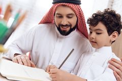 Arabski ojciec uczy małego syna pisownia listy obraz stock