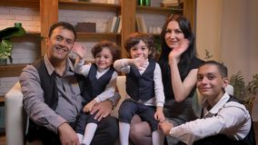 Arabski rodzinny obsiadanie na kanapie i smilingly witać z kamerą w żywym pokoju zbiory