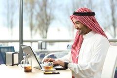 Arabski saudyjski mężczyzna pracuje online z laptopem fotografia royalty free