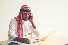 Arabski saudyjski mężczyzna pracuje online z laptopu i wezwania ing smartph fotografia royalty free