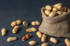 Arachid w nutshell w burlap worku lub parciak na drewnianym tle skład arachidy fotografia stock