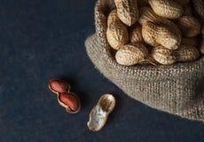 Arachid w nutshell w burlap worku lub parciak na drewnianym tle skład arachidy obraz stock