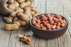 Arachid w nutshell w i pucharze na drewnianym tle burlap parciaku lub worku skład arachidy zdjęcie royalty free