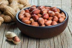 Arachid w nutshell w i pucharze na drewnianym tle burlap parciaku lub worku skład arachidy fotografia royalty free