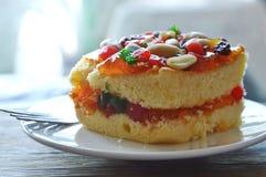 Arachide della guarnizione del dolce del burro ed insalata arancio della frutta secca con la forcella sul piatto fotografia stock libera da diritti