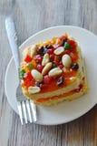 Arachide della guarnizione del dolce del burro ed insalata arancio della frutta secca con la forcella sul piatto immagine stock
