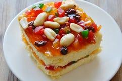 Arachide della guarnizione del dolce del burro ed insalata arancio della frutta secca sul piatto fotografia stock