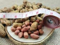 Arachide o arachide su un piatto di legno con nastro adesivo di misurazione Fotografie Stock Libere da Diritti