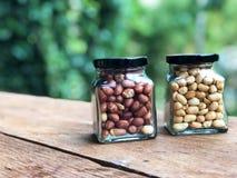 Arachides épluchées dans une bouteille, le noir de capsule Mettez dessus une table en bois avec le fond vert photos stock