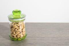 Arachides dans un pot sur une table en bois photos stock