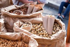 Arachidi, pistacchi e mandorle salati in un primo piano dei sacchi di carta Alimento della via Fotografia Stock Libera da Diritti