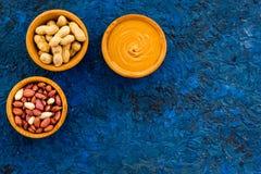 Arachidowy pasty pojęcie Puchary z masłem, dokrętki w skorupie, obrane dokrętki na błękitnej tło odgórnego widoku kopii przestrze Obrazy Royalty Free