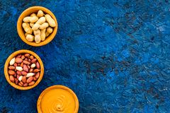Arachidowy pasty pojęcie Puchary z masłem, dokrętki w skorupie, obrane dokrętki na błękitnej tło odgórnego widoku kopii przestrze Fotografia Royalty Free